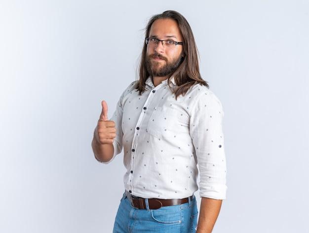 Ernstige volwassen knappe man met een bril die in profielweergave staat en duim omhoog laat zien