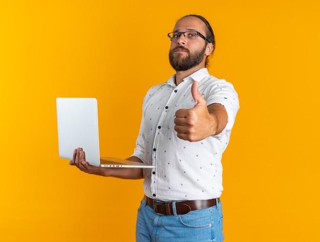 Ernstige volwassen knappe man met een bril die in profielweergave staat en naar een camera kijkt die een laptop vasthoudt met duim omhoog geïsoleerd op een oranje muur