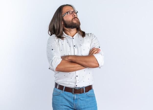 Ernstige volwassen knappe man met een bril die staat met gesloten houding en omhoog kijkt geïsoleerd op een witte muur met kopieerruimte