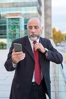 Ernstige volwassen leidinggevende met smartphone lezen bericht