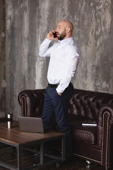 Ernstige volwassen man in een wit overhemd is praten over de telefoon