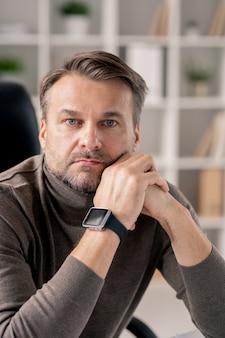 Ernstige volwassen man met smartwatch op rechterpols op zoek naar jou zittend door werkplek op kantoor