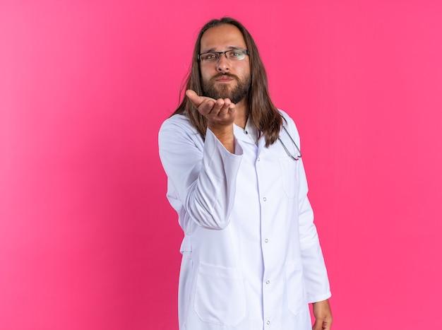 Ernstige volwassen mannelijke arts met een medisch gewaad en een stethoscoop met een bril die naar de camera kijkt en een klapkus verzendt die op een roze muur met kopieerruimte wordt geïsoleerd