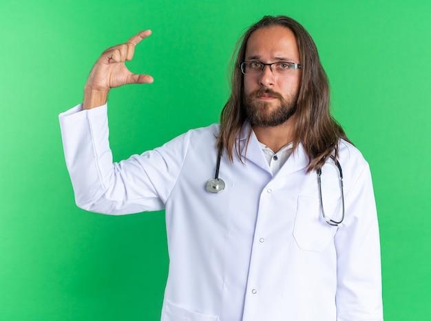 Ernstige volwassen mannelijke arts met een medisch gewaad en een stethoscoop met een bril die naar de camera kijkt en een klein gebaar doet dat op een groene muur is geïsoleerd