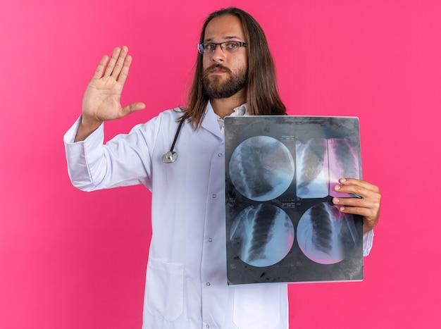 Ernstige volwassen mannelijke arts met een medisch gewaad en een stethoscoop met een bril met een röntgenfoto die naar een camera kijkt die een stopgebaar doet dat op een roze muur wordt geïsoleerd