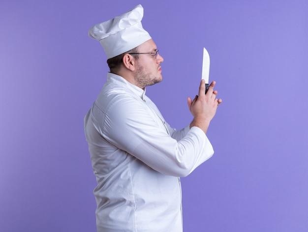 Ernstige volwassen mannelijke kok met een uniform van de chef-kok en een bril die in profielweergave staat en naar mes kijkt geïsoleerd op paarse muur met kopieerruimte