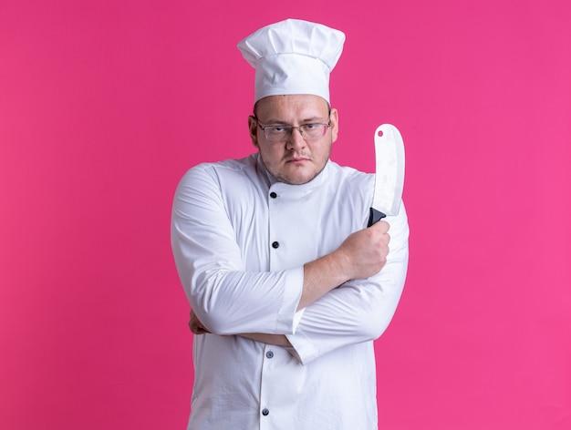 Ernstige volwassen mannelijke kok met een uniform van de chef-kok en een bril die met een gesloten houding staat en een hakmes vasthoudt die naar de voorkant kijkt geïsoleerd op een roze muur met kopieerruimte