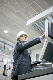 Ernstige volwassen mannelijke plantingenieur die industriële machine bedient, op knoppen op het bedieningspaneel drukt, tablet vasthoudt