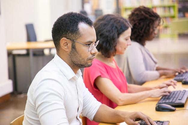 Ernstige volwassen mannelijke student die in computerklasse bestudeert