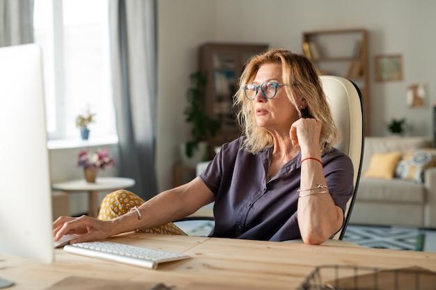 Ernstige volwassen vrouw of zakenvrouw in vrijetijdskleding zit door bureau achter computermonitor tijdens het werken op afstand thuis