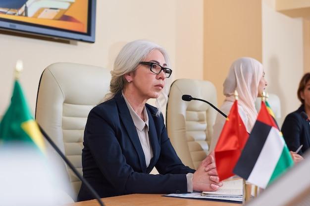 Ernstige volwassen vrouwelijke afgevaardigde in elegant pak luisteren naar vragen van het publiek voordat ze deze op de conferentie beantwoorden