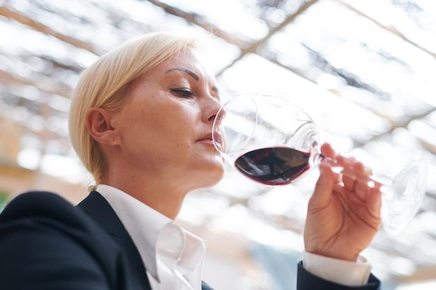 Ernstige volwassen wijnmaker die bokal rode wijn bij haar neus houdt terwijl ze de geur evalueert