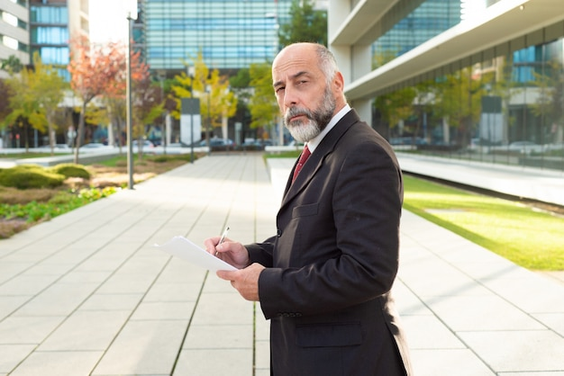 Ernstige volwassen zakenman met papieren