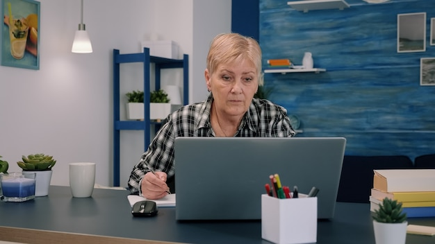 Ernstige volwassen zakenvrouw van middelbare leeftijd met behulp van laptop e-mail typen en schrijven op notebook, werken op kantoor aan huis, gerichte senior oude dame informatie zoeken op internet of online communiceren
