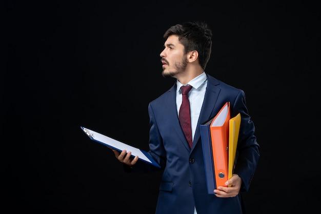 Ernstige volwassene in pak die verschillende documenten vasthoudt en ergens op een geïsoleerde donkere muur kijkt