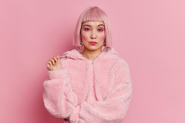 Ernstige vrij aziatische vrouw met trendy roze haar gekleed in winterjas heeft heldere, levendige make-up houdingen