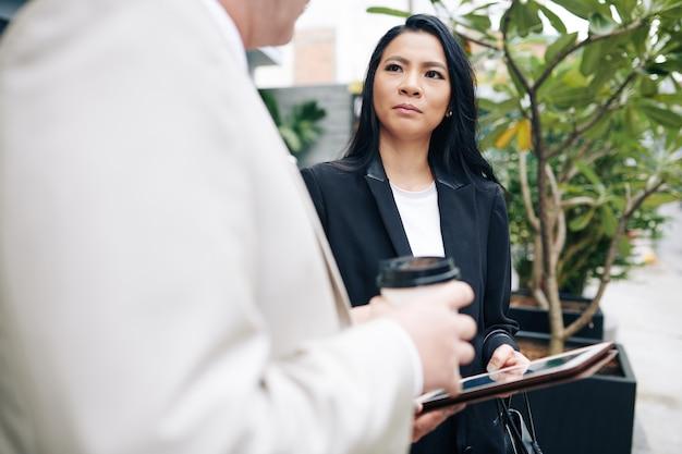 Ernstige vrij aziatische zakelijke dame die met tabletcomputer haar pratende hogere collega bekijkt