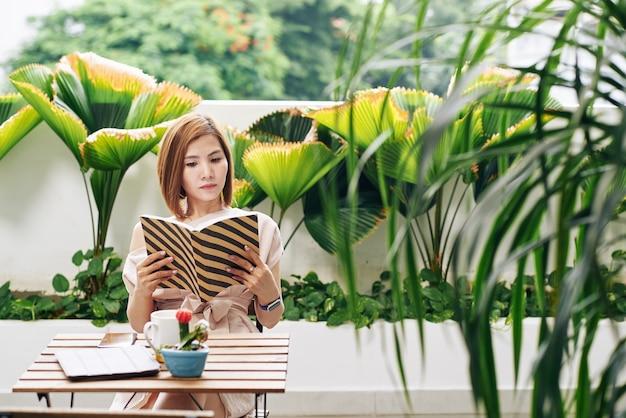 Ernstige vrij jonge aziatische vrouw die aan koffietafel rust en boeiend boek leest