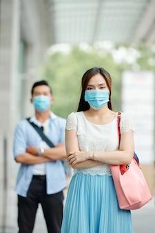 Ernstige vrij jonge vietnamese vrouw die zich in straat met medisch masker op haar gezicht bevindt