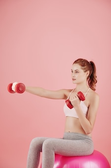 Ernstige vrij jonge vrouwenzitting op roze geschiktheidsbal en oefening met domoren