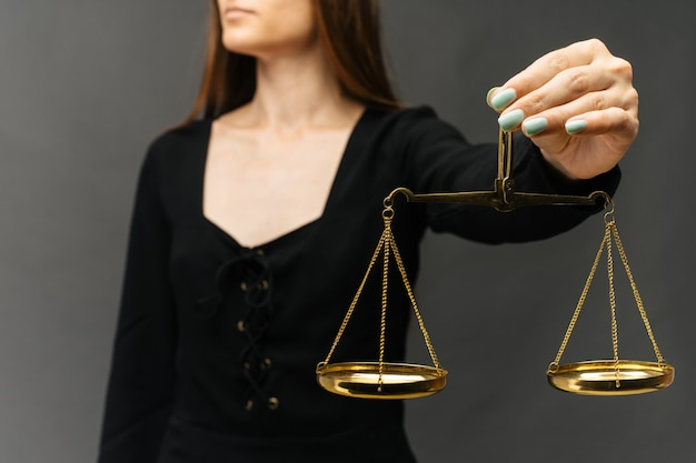 Ernstige vrouw die de rechtvaardigheidsschaal op donkere achtergrond houdt