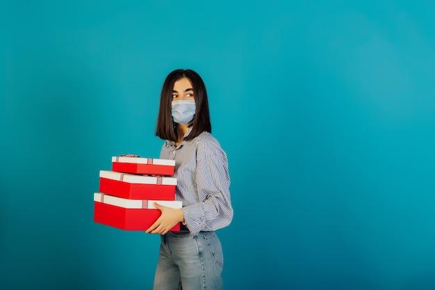 Ernstige vrouw die gezichts medisch chirurgisch masker draagt, houdt drie geschenkdoos geïsoleerd op blauw oppervlak.