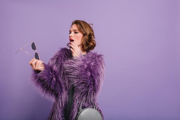Ernstige vrouw die in trendy paars jasje haar donkere zonnebril in hand bekijkt
