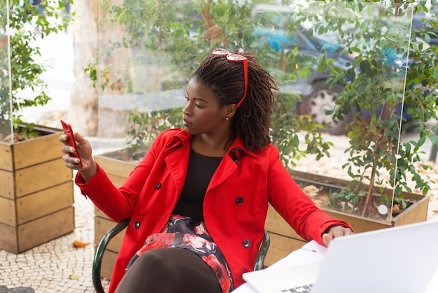 Ernstige vrouw die laptop en smartphone in restaurant gebruiken