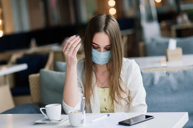 Ernstige vrouw die met beschermend gezichtsmasker nieuws op een koffieterras controleert