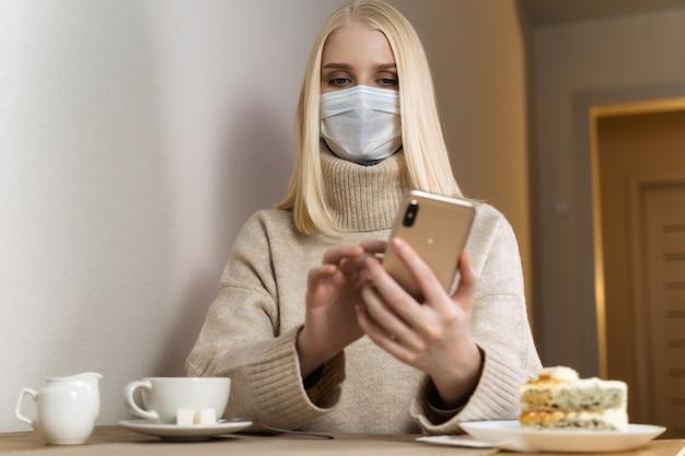 Ernstige vrouw die met beschermend gezichtsmasker slimme telefoon bekijkt die nieuws over een koffie controleert.