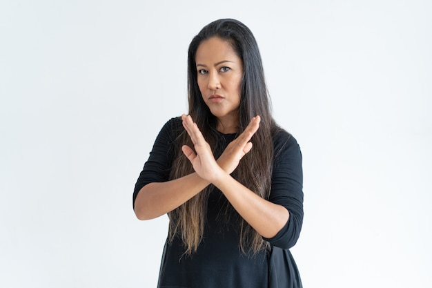 Ernstige vrouw die op middelbare leeftijd gekruiste handen toont