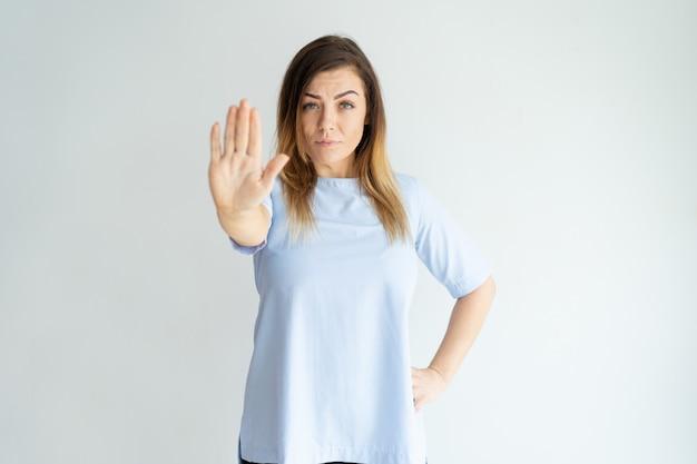 Ernstige vrouw die open palm of eindegebaar toont en camera bekijkt.