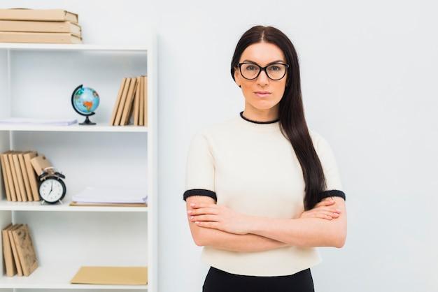 Ernstige vrouw die zich in bureau met gekruiste wapens bevindt