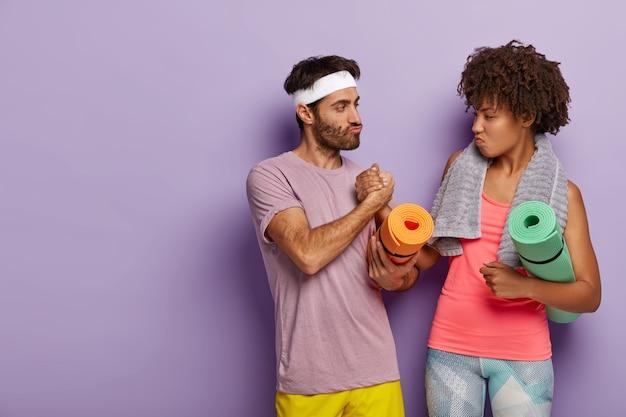 Ernstige vrouw en man van gemengd ras houden elkaars hand vast, ontmoeten elkaar in de sportschool, trainen samen, dragen fitnessmatten
