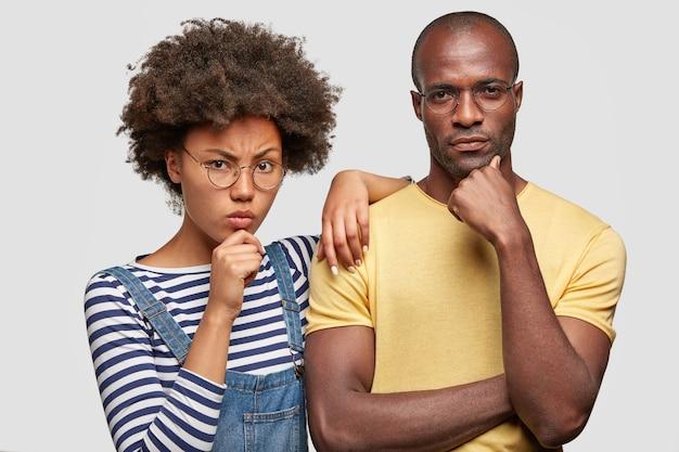 Ernstige vrouw en vriend houden kin vast, gericht op camera, hebben ontevreden uitdrukkingen