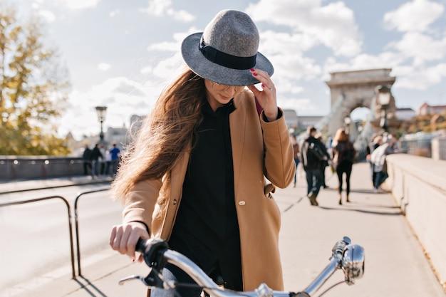 Ernstige vrouw in trendy beige jas rijden door de stad in herfstochtend