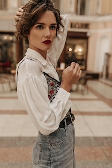 Ernstige vrouw in wit overhemd en spijkerbroek met zwarte band op zoek weg in de stad. brunette vrouw met heldere lippen poseren op straat.