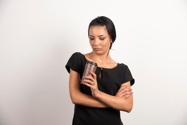Ernstige vrouw kijken naar kopje koffie op witte muur.