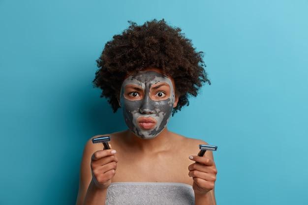 Ernstige vrouw met afrohair geconcentreerd op iets heel aandachtig, past kleimasker toe om rimpels te verminderen, houdt scheermes vast en heeft hygiënische procedures na het nemen van een douche geïsoleerd op blauwe muur