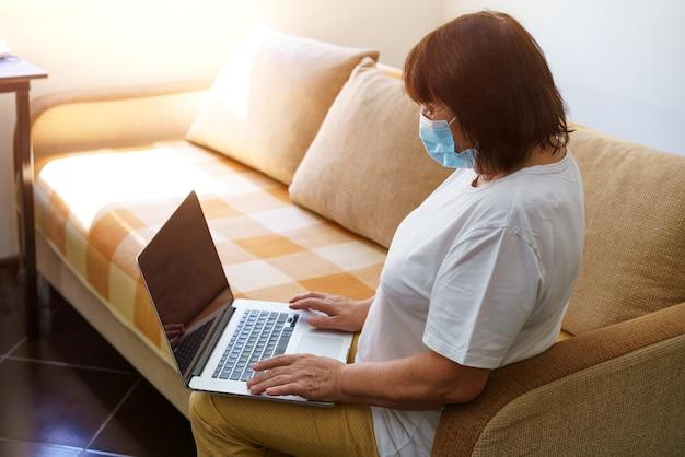 Ernstige vrouw met beschermend masker gebruikt laptop en controleert e-mail op internet terwijl ze op de bank zit te kijken...