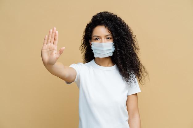 Ernstige vrouw met donkere huid maakt stopgebaar, draagt een medisch griepmasker, vraagt thuis te blijven om de coronavirusziekte niet te verspreiden, voorkomt virus
