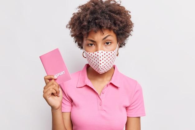 Ernstige vrouw met krullend haar heeft een paspoort dat op reis gaat en draagt een beschermend masker omdat bescherming tegen coronavirus infectie voorkomt die over een witte muur wordt geïsoleerd