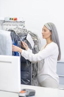 Ernstige vrouw met lang grijs haar in lichte kleding met instructies in de buurt van rek met kleding in de stomerij