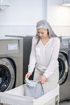 Ernstige vrouw met lang grijs haar in lichte kleren met t-shirt in haar handen die zich in wasserij bevinden