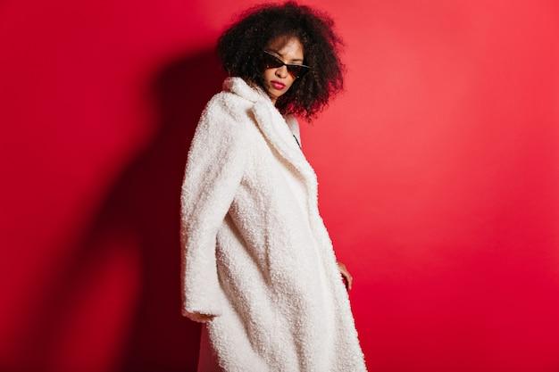 Ernstige vrouw poseren in zonnebril en jas