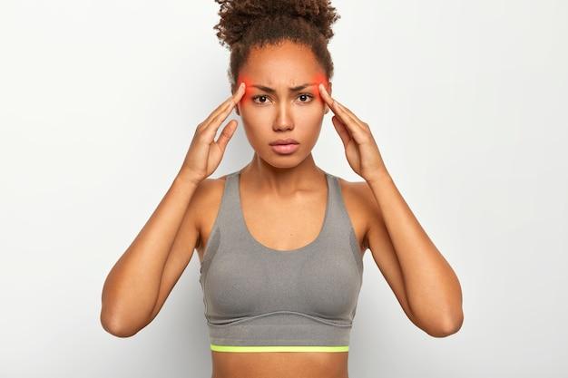 Ernstige vrouw raakt beide slapen aan, lijdt aan migraine, draagt een grijze top, heeft rood gemarkeerde zones op het hoofd met een pijnlijke plek