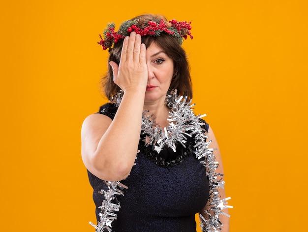 Ernstige vrouw van middelbare leeftijd die de hoofdkrans van kerstmis en klatergoudslinger om hals draagt die camera bekijkt die de helft van gezicht bedekt met hand die op oranje achtergrond wordt geïsoleerd