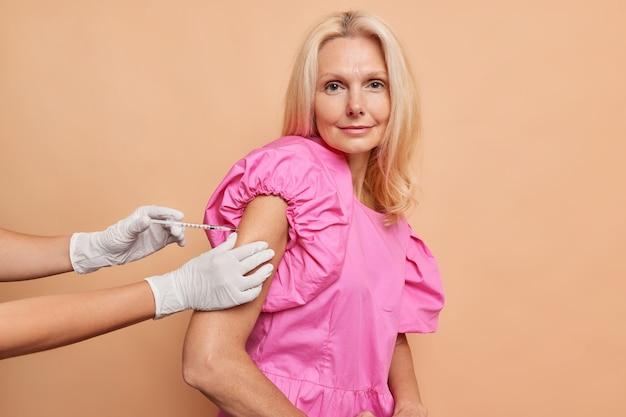 Ernstige vrouw van middelbare leeftijd kijkt recht in de camera terwijl ze een covid-vaccin krijgt en een modieuze roze jurk draagt