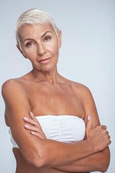 Ernstige vrouw van middelbare leeftijd met gekruiste armen poseren op camera