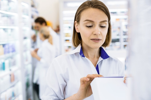 Ernstige vrouwelijke apotheker die een drug in haar handen houdt die de aandachtige samenstelling van de drug bekijkt
